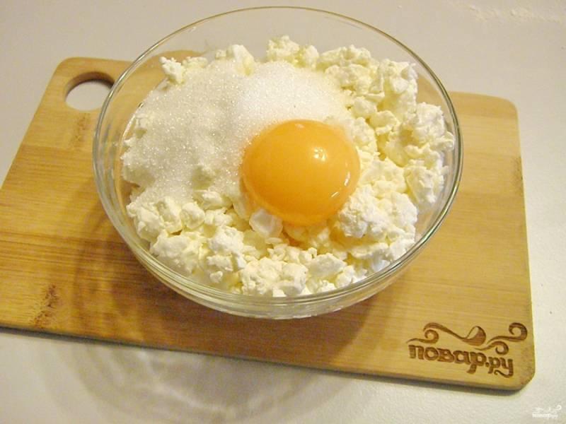 Для начинки слоек смешайте творог с желтком яйца и сахаром. Смешивать лучше вилочкой, чтобы попутно разбивать творожные комочки.