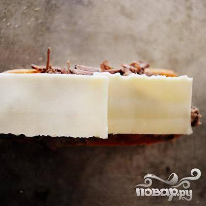 Поверх мяса кладем пару кусочков сыра.