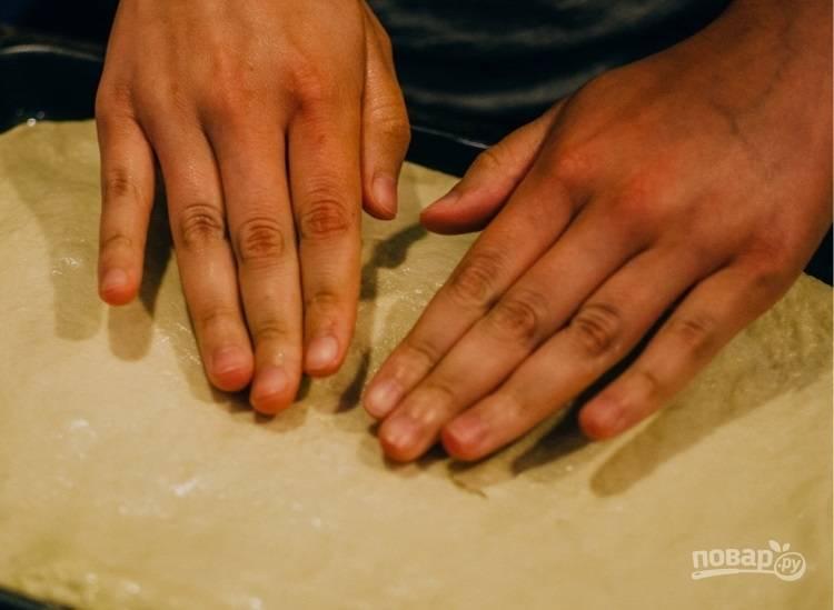 8.Подготовьте противень, переложите на него тесто и руками растяните его в пласт по ширине противня. Оставьте тесто на 30-40 минут.