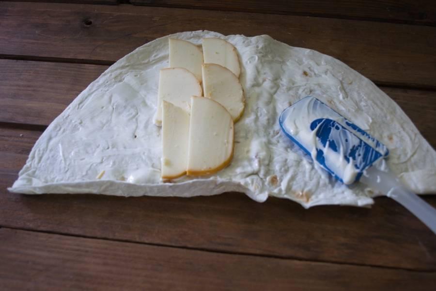На серединку лаваша выложите нарезанный сыр. Форма нарезки зависит от упаковки сыра. Мой круглый. Нарезала тонко, плоскими полукольцами.
