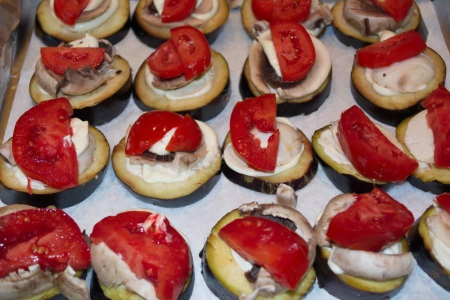 Чтобы грибы лучше лежали, я слегка смазала каждый кружочек баклажана майонезом (можно использовать сметану). На каждый гриб выложите по кусочку помидора.