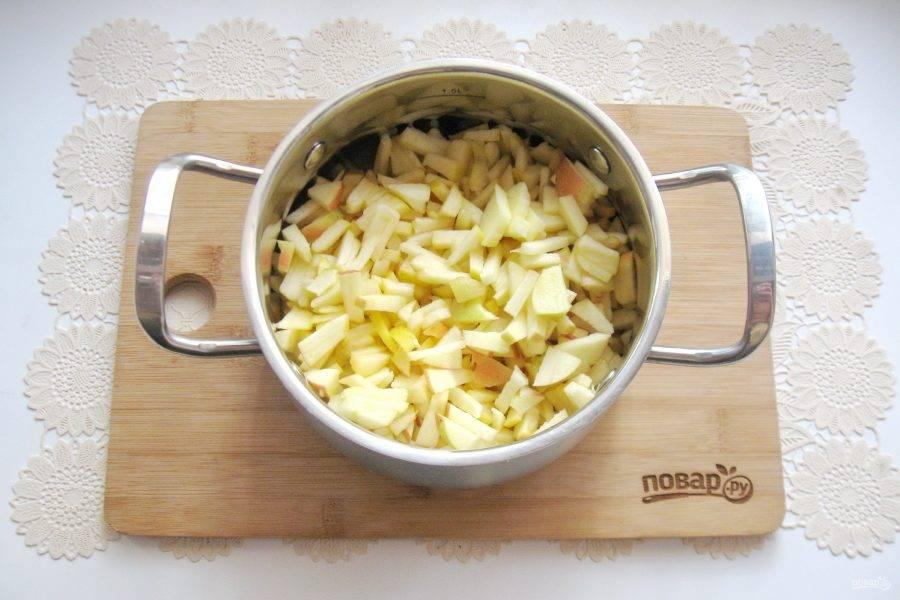 Выложите нарезанные яблоки в кастрюлю.