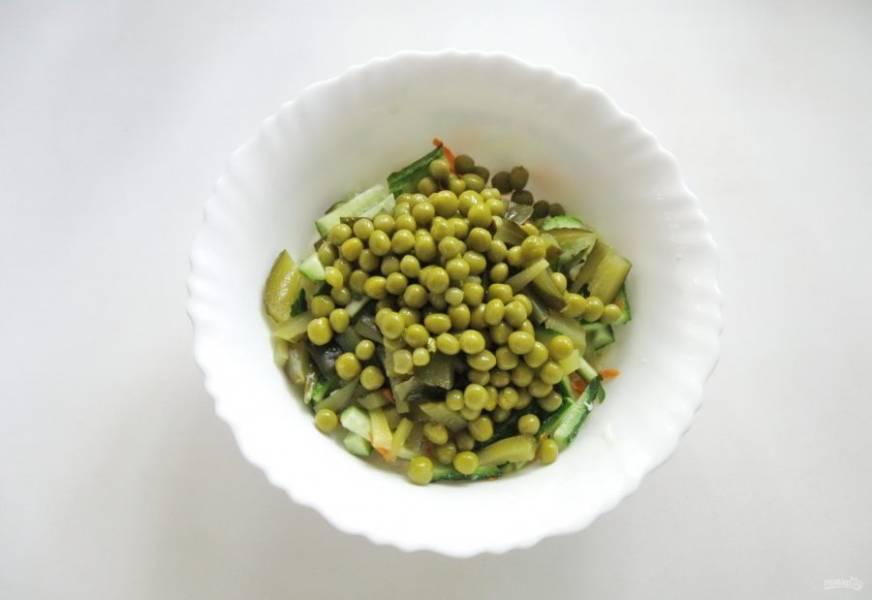 Выложите в салат консервированный зеленый горошек.