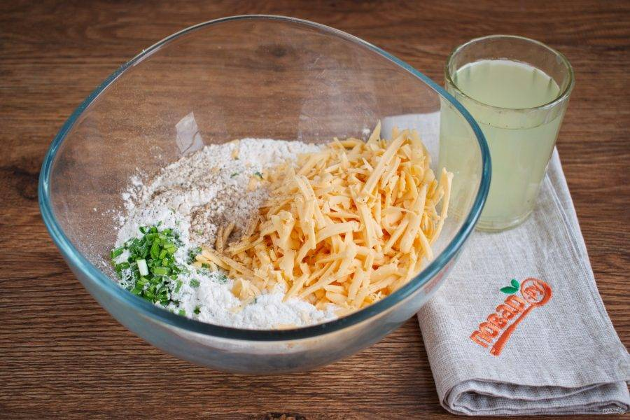 Муку просейте в миску. Зеленый лук измельчите. Холодное сливочное масло натрите на крупной терке или мелко порубите ножом.  Соедините все ингредиенты, кроме сыворотки, в миске, перемешайте. Влейте сыворотку, замесите мягкое тесто. Заверните его в пищевую пленку, поместите в холодильник на 10 минут. За это время разогрейте духовку до 200 градусов.