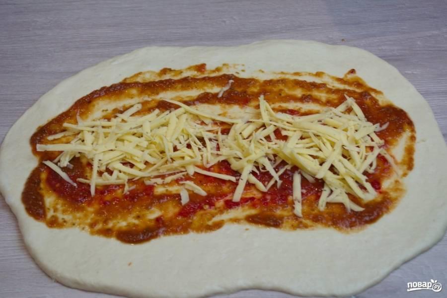 5. Натрите на терке твердый сыр. Часть сыра мы выложим нижним слоем, а часть — сверху на начинку. Итак, натертый сыр выкладываем на томатный соус. Учтите, что сыр нужно разделить на 3 части, ибо из этого количества теста выйдет 3 пиццы стромболи.