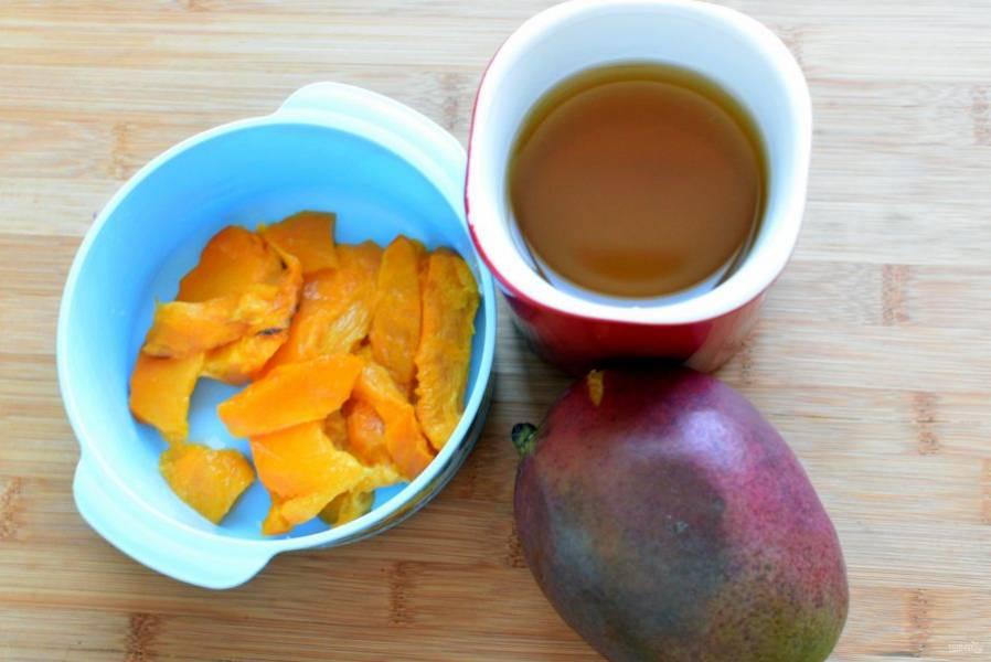Из готовой тыквы извлеките ложкой нужное количество мякоти. Заварите зеленый чай – лучше всего без всяких добавок. Дайте ему настояться, но не слишком долго, чтобы напиток не горчил.  Очистите половинку спелого манго. Добавьте очищенный печеный чеснок. Пюрируйте тыкву и манго погружным блендером, залив горячим чаем.