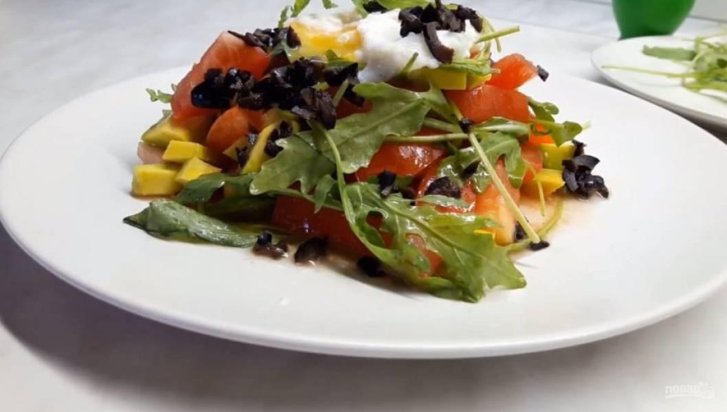 4. К салату добавьте рукколу, перемешайте и выложите на тарелку. Сверху аккуратно выложите яйцо пашот, очень мелко нарезанные маслины. Во время подачи разрежьте желток, чтобы он вытек. Приятного аппетита!