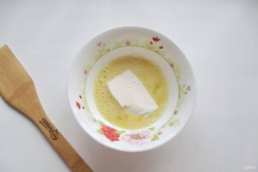 Обмакните кусочки сыра в яйце со всех сторон.