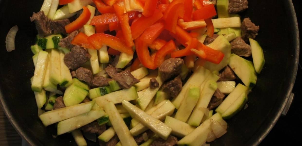Затем чистим и режем цуккини и перец полосками, также добавляем в сковороду к мясу.