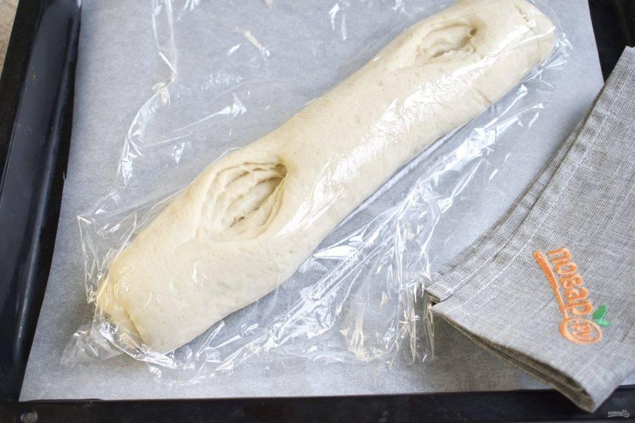 Выложите на противень, застеленный пергаментом для выпечки. От края батона отступите 2-3 см и острым ножом сделайте  надрез (8-10 см)  до самого низа заготовки, то же самое сделайте с другой стороны батона. Накройте заготовки пленкой и уберите в теплое место для расстойки на 40-50 минут.