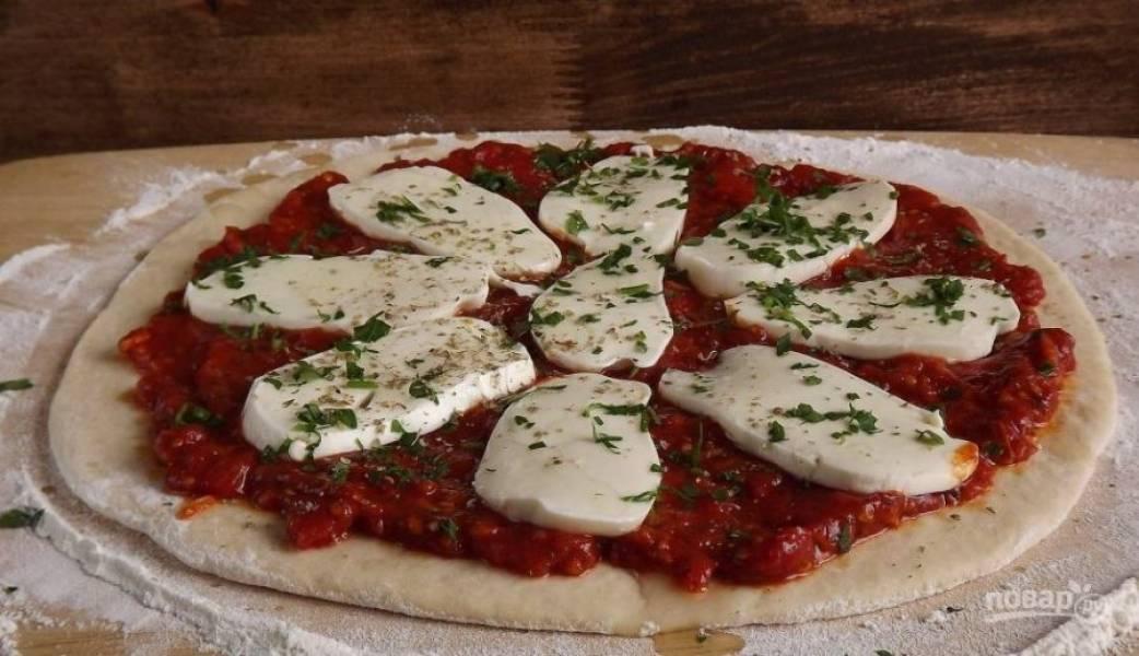Моцареллу нарежьте на крупные куски и выложите на томатный соус. Затем положите листики свежего базилика, измельченного ножом, и запекайте пиццу при температуре двести пятьдесят градусов десять минут.