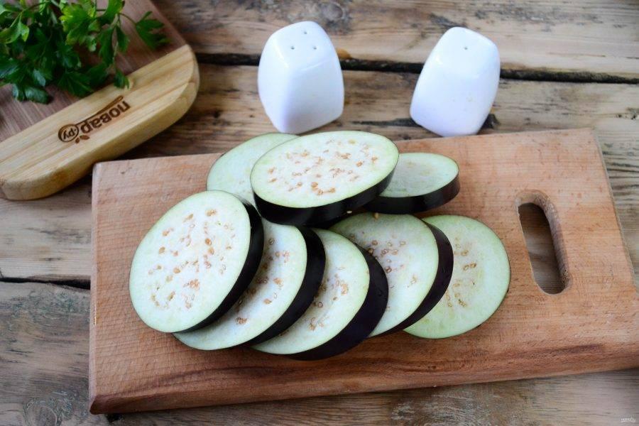 Баклажан порежьте на кружочки толщиной 8-10 мм. Посолите баклажаны, сложите в миску и оставьте на 30 минут, затем промойте кружочки баклажанов и просушите. Это нужно делать, чтобы баклажаны не горчили в готовом блюде.