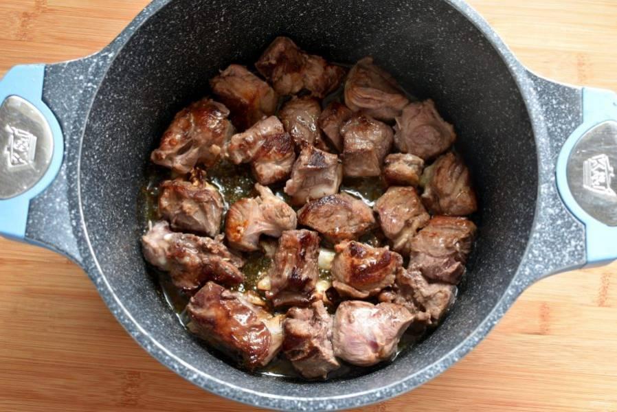 Баранину нарежьте крупными кубиками, косточки порубите. Разогрейте масло в казане или жаровне с толстым дном  до дымка и обжарьте мясо до румяной корочки со всех сторон.