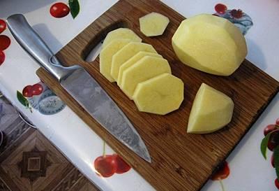 При помощи ножа очищаем картошку от кожуры и  хорошо промываем под проточной водой. Просушиваем картофель с помощью бумажного полотенца и перекладываем его на разделочную доску. При помощи  ножа нарезаем корнеплоды поперек на небольшие по толщине кусочки,  чтобы они запеклись одновременно с мясом и не пригорели у основания противня.