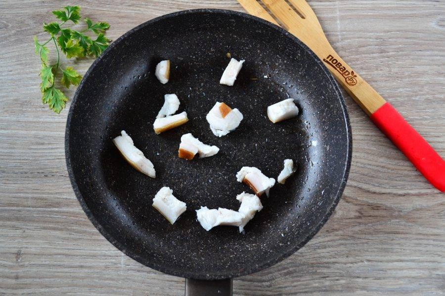 Сало порежьте на небольшие кусочки. Можете взять больше сала, но тогда блюдо получится очень жирным. Отправьте сало в сковороду и поставьте на огонь, чтобы оно начало топиться.