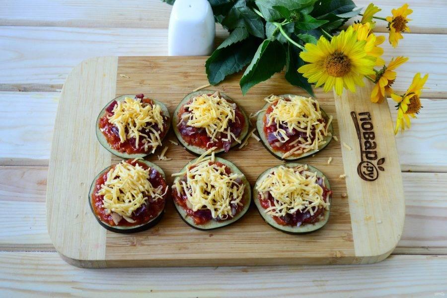 Твердый сыр натрите на мелкой терке. Обильно присыпьте сыром кружочки баклажанов. Должны получиться прям красивые высокие горки.
