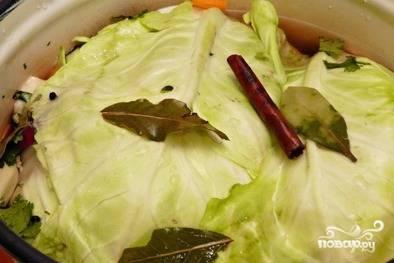 Далее залейте бочку остывшим рассолом, а сверху положите пару листьев капусты. Закройте её тарелкой, а сверху поставьте груз.