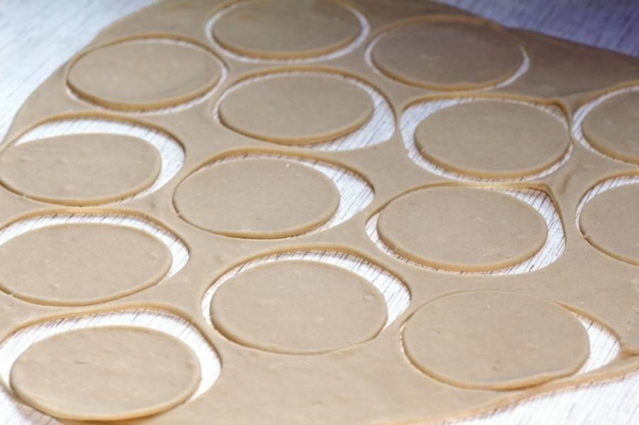 Готовое тесто раскатываем в тонкий пласт и вырезаем из него кружочки при помощи стакана.