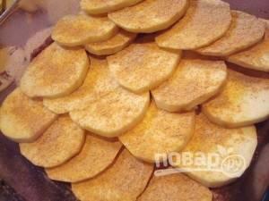 Картофель почистите, помойте и нарежьте кружочками. Распределите их по фасоли. Сверху насыпьте приправу.