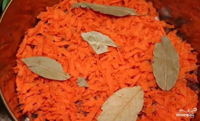 Морковь трем на крупной терке и распределяем равномерным слоем по мясу. Добавляем лавровый лист и уксус.
