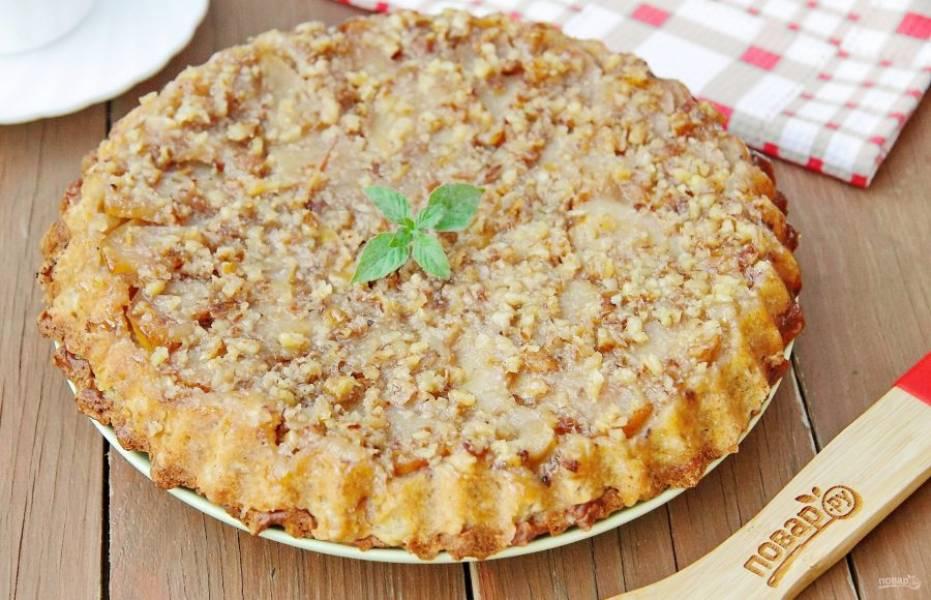 Дайте пирогу немного остыть в форме, после чего переверните аккуратно на тарелку дном вверх и снимите пергамент. Сверху должны оказаться нежные и сочные яблоки с орехами в карамельном соусе. Яблочный пирог для веганов готов.