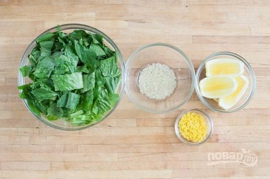 1.Мою салат и отрезаю корень, оставшиеся листочки рву руками или измельчаю крупно ножом. Снимаю цедру с лимона, чеснок чищу и пропускаю через пресс, смешиваю с уксусом.