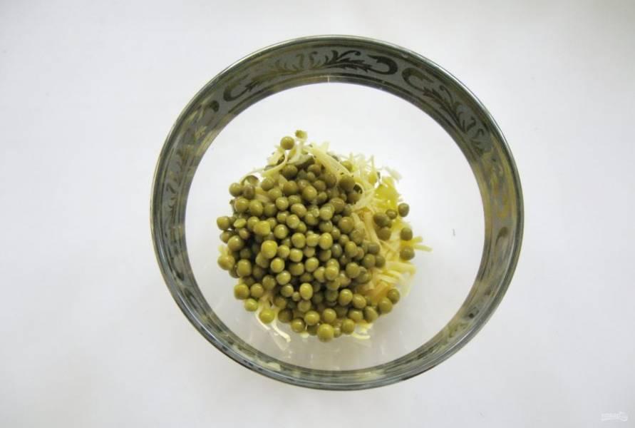 Выложите в салатник консервированный зеленый горошек.