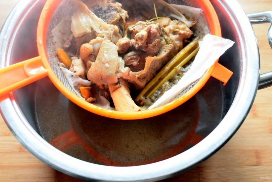 Перед дальнейшим приготовлением, бульон тщательно процедите через ситечко или марлю. Мясо отделите от костей и нарежьте кусочками. Овощи из бульона выбросите.