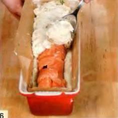 Завернуть края лосося поверх начинки. Сверху уложить пюре белой рыбы. Накрыть куском промасленного пергамента. Готовить в течении часа в нагретой до 180 °С духовке. Дать остыть, изъять из формы и порезать на куски.
