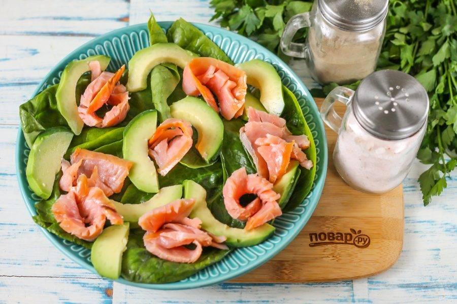 Вскройте упаковку со слабосоленой горбушей, выложите ломтики рыбы между нарезкой авокадо.