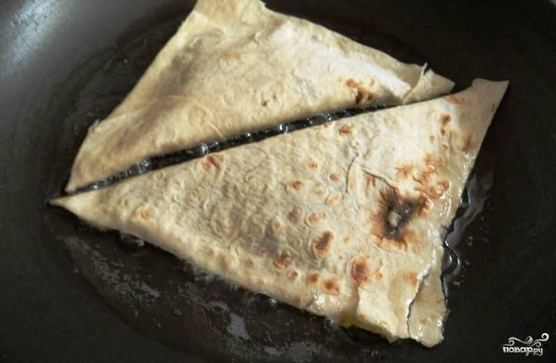 Возьмите чистую сухую сковородку, влейте на нее достаточное количество масла. Оно должно быть рафинированным, без запаха. Если хотите, то можете заменить его на сливочное масло. Раскалите сковороду на сильном огне, затем сделайте огонь маленьким и выложите на сковородку конвертики.