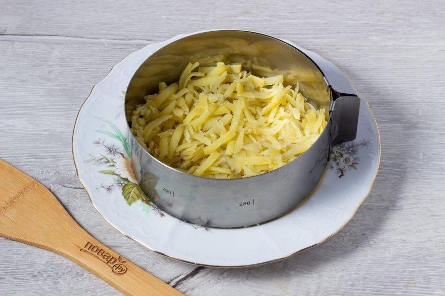 Первым слоем салата выложите картофель натертый на крупной терке и майонез.