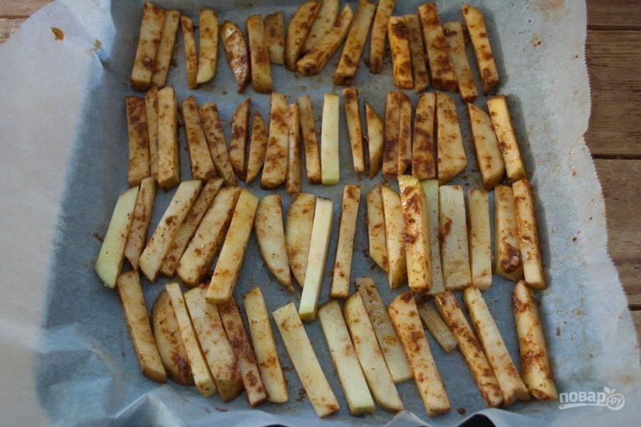 Влейте к картофелю пару ложек растительного масла и перемешайте. Выложите картофель (каждый кусочек отдельно от другого) на противень, застеленный пергаментом. Разогрейте духовку до 200 градусов. Запекайте картофель в духовке 30 минут.
