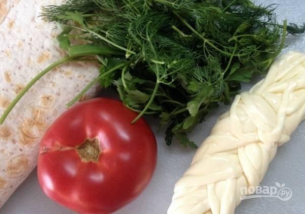 1. Всего два основных ингредиента можно считать обязательными: лаваш и сыр. Все остальное можно смело назвать вашей импровизацией. В данном случае закуска дополнена помидором и свежей зеленью.