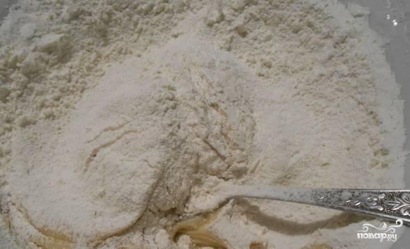 Затем добавьте просеянную муку. Замешайте песочное тесто.