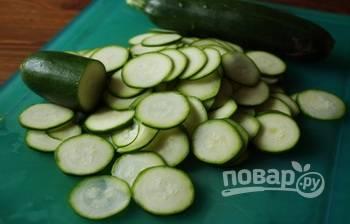 Цуккини вымойте под проточной водой. Очищать его не нужно. Отрежьте у овощей кончики с обеих сторон и нарежьте цуккини на кружочки толщиной в полсантиметра.