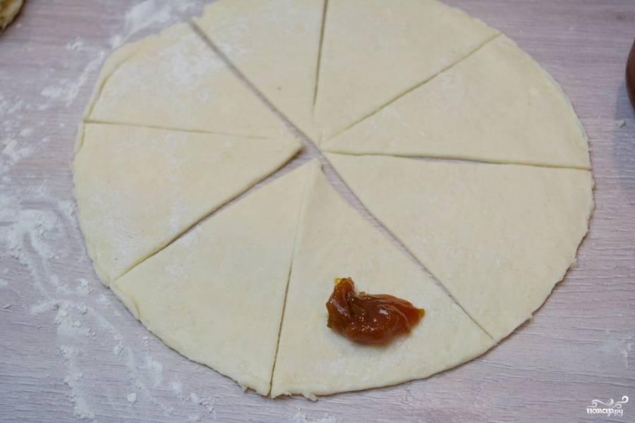 На край сектора выложите ложку варенья, сверните тесто в рулетик (от широкого края — к узкому).