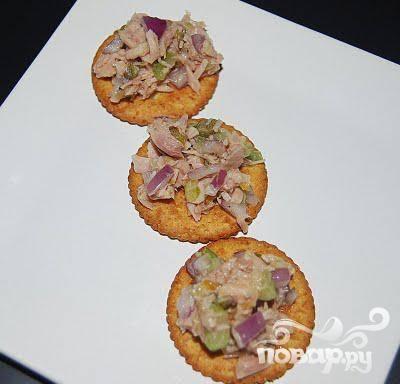 3. На хлебец выложите 2 ложки салата из тунца так, чтобы он закрывал всю поверхность основы канапе.