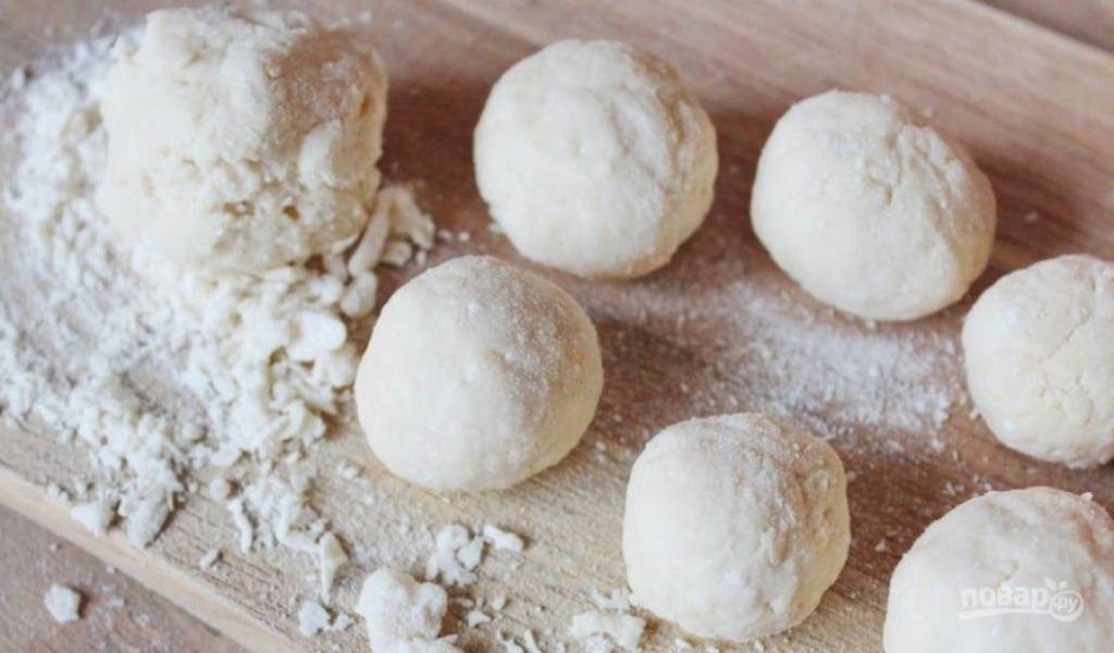 Из полученного теста скатайте жгут, присыпав рабочую поверхность мукой. Затем разделите его на небольшие кусочки и скатайте из теста шарики размером с грецкий орех.