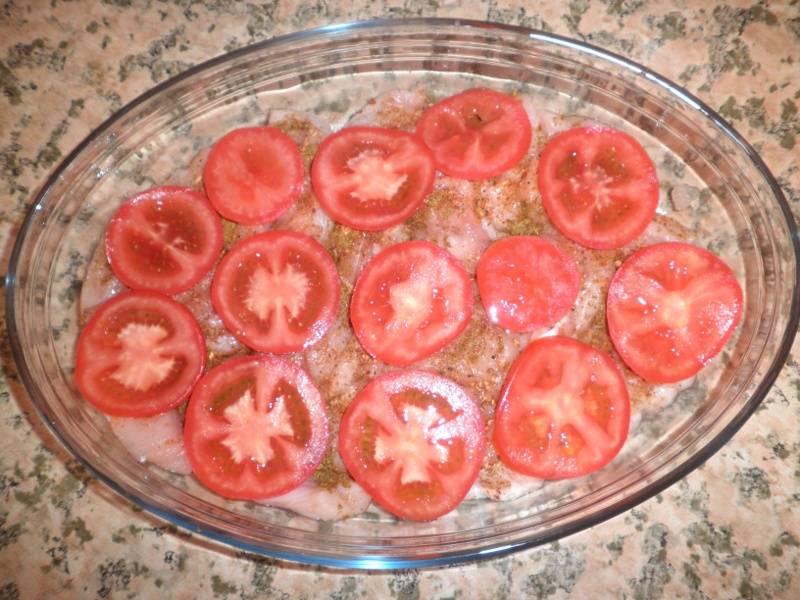 Смазываем курицу майонезом, а сверху выкладываем колечки помидоров.