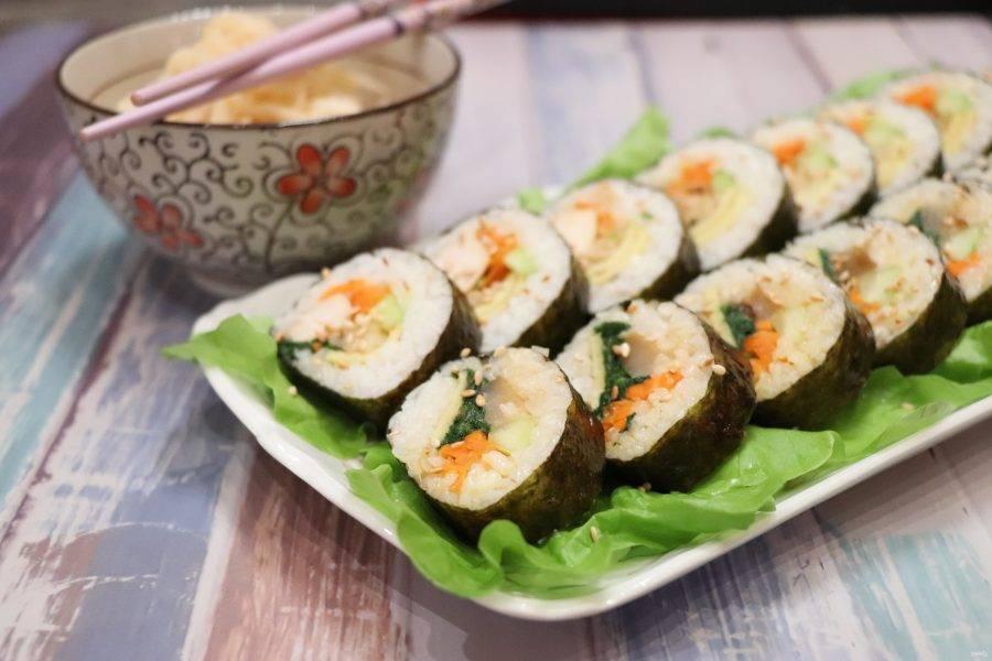 Кимбап нарежьте на кусочки толщиной 1,5 см и посыпьте их обжаренным кунжутом. Обычно кимбап не подают с соевым соусом, в отличие от японских роллов, так как начинка благодаря квашенным овощам получается сочной, соленой и острой. Приятного аппетита!