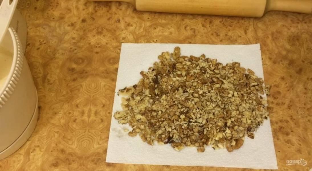 2. Добавьте просеянную муку и взбейте миксером до однородности. Грецкие орехи измельчите скалкой между двумя листами бумажного полотенца.