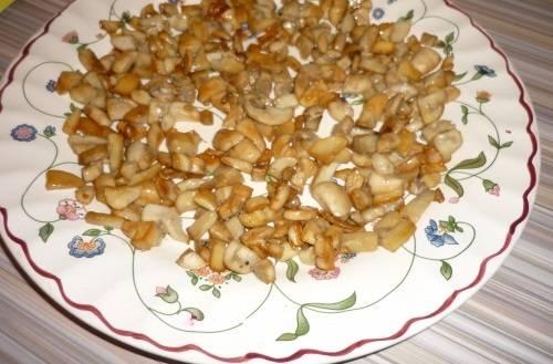 1. Перед готовкой надо отварить курицу и яйца, а грибы обжарить с луком и остудить. Выкладываем на дно салатницы остывшие грибы.