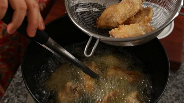 Достаньте кусочки курицы и переложите их в сито. Избавьтесь от лишнего масла. Дайте крылышкам полежать пару минут.