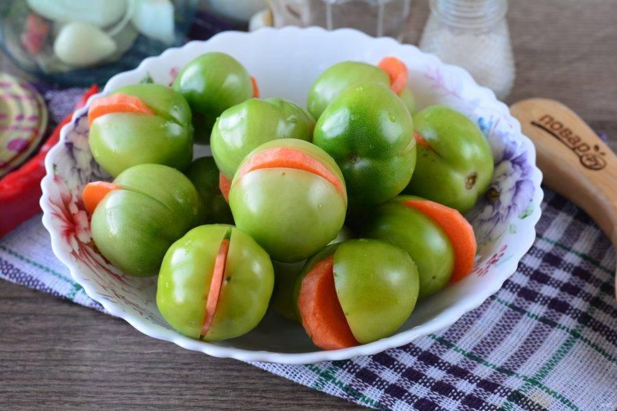 Сделайте надрезы на помидорах и вложите туда морковку.