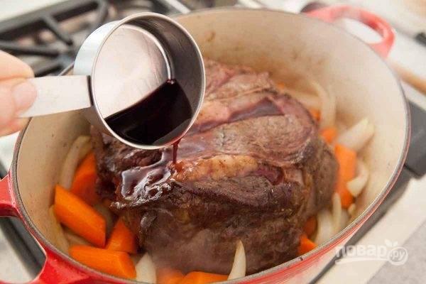 4.Выложите поверх овощей обжаренное мясо, добавьте вино и лавровый лист.