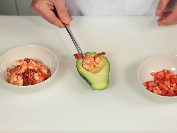 Перед подачей очистите креветки от маринада. Уложите их в половинки авокадо с помидорами. Полейте соусом.