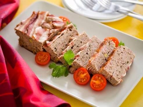 Спустя сутки блюдо можно подавать к столу, нарезав его ломтиками толщиной 1-2 см. и украсив свежей зеленью и дольками помидора.