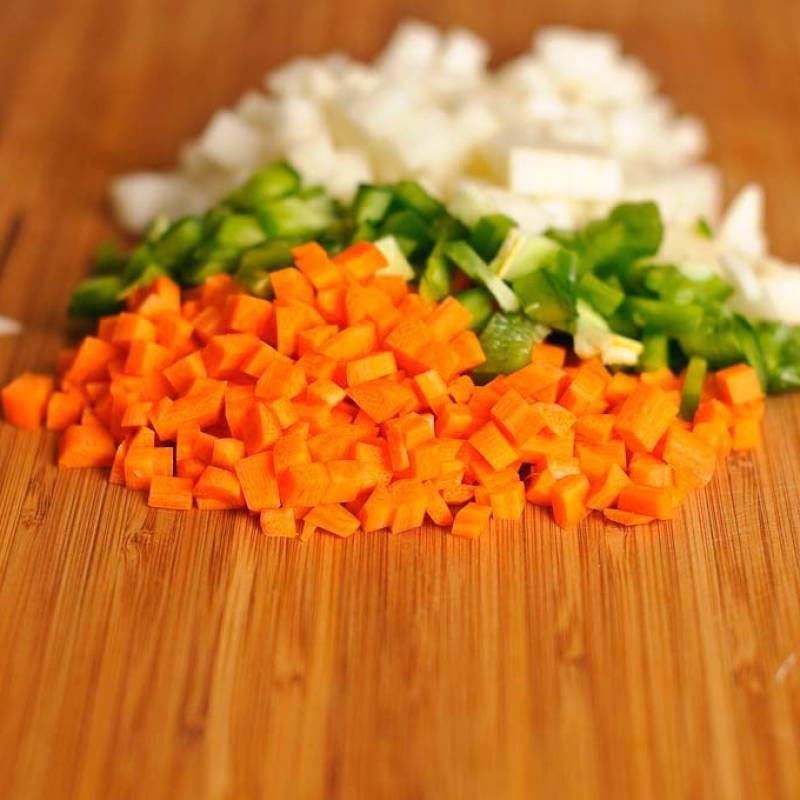 Промыть, почистить овощи  (морковь, перец, картофель, помидор и чеснок). Затем, нарезать небольшими кубиками. Отложить в сторону.