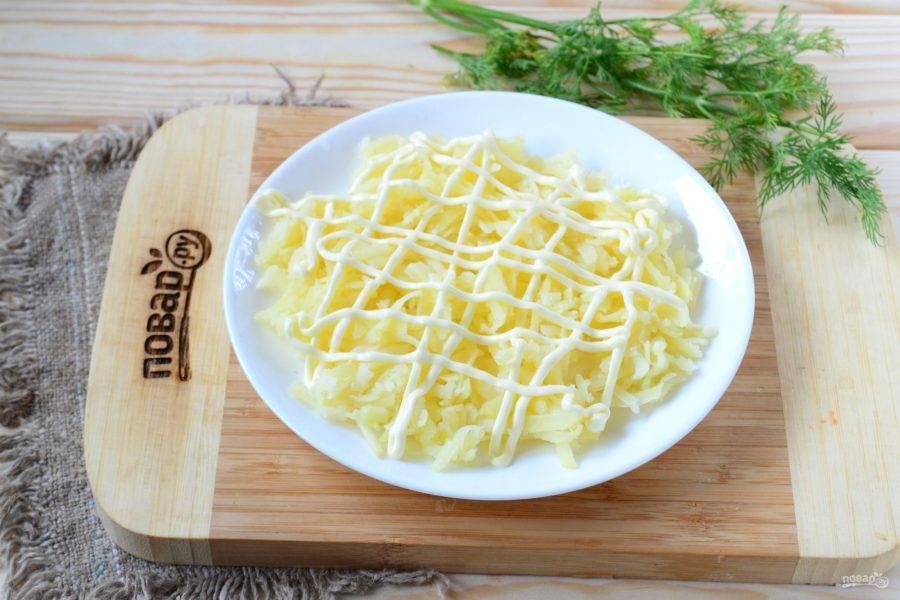 На крупной терке натрите картофель, выложите на плоскую тарелочку, подходящую по размеру. Сверху покройте майонезной сеточкой.